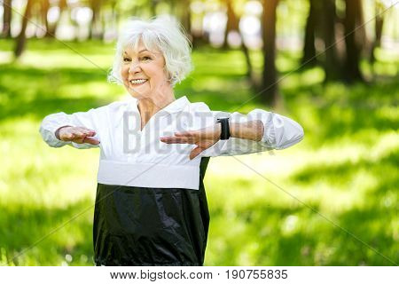 Waist up portrait of old cheerful lady doing warming up exercises in summer forest. She is holding hands bent in front of her body at chest level and smiling