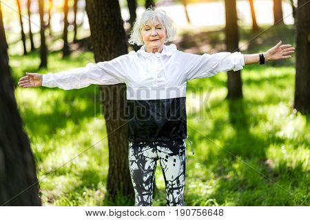 Cheery senior lady is standing still with closed eyes and keeping arms stretched to sides. She is meditating among forest trees