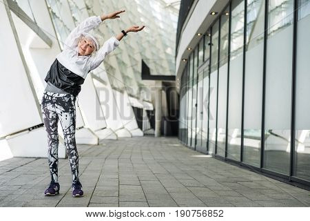Full length portrait of happy old woman doing exercises near high constructions. She is standing on pathway with hands up and making bend to side. Copy space in right side