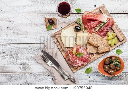Typical italian antipasto, wooden cutting board with prosciutto, ham, cheese and olives on white wooden background. Top view with copy space