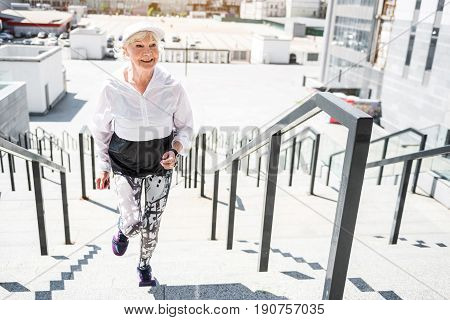 Happy old lady is climbing upstairs huge city ladder with metal handrails. She is doing cardio exercises. Copy space in right side