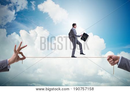 Businessman walking on tight rope in business concept