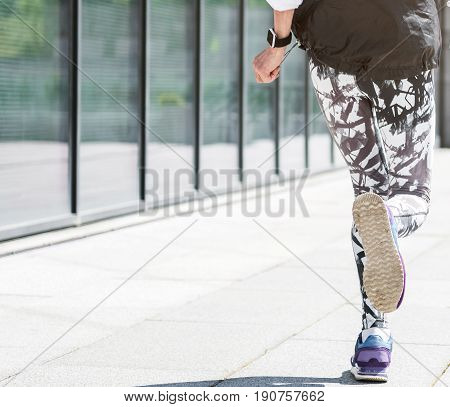 Close up of legs of old woman jogging near huge windows of office building. Focus on sneakers and sole. Copy space in left side