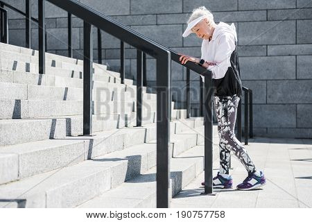 Tired elderly lady is standing near metal handrails of big ladder construction, leaning on it by her hand and looking down. She is going to go on climbing up