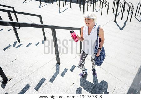 Top view of cheery senior woman raising up big city ladder construction with metal handrails. She is holding bottle of water in one hand. Copy space in left side