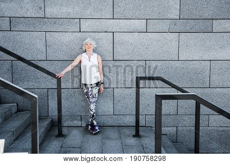 Full length portrait of happy elderly woman standing by wall cross-legged. She is touching by hand metal guard rail of big stadium ladder and smiling