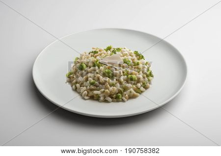 Risotto dish with barley spelt broccoli and cheese isolated on white table