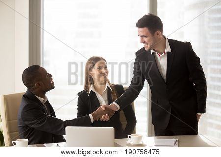 Afro american and caucasian businessmen handshaking at formal meeting, friendly african entrepreneur welcoming new partner before after negotiations, shaking hand, successful international partnership