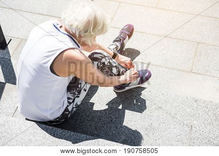 Top view of elderly woman tying her laces on sneakers. She is sitting on granitical steps and going to start exercise outdoor
