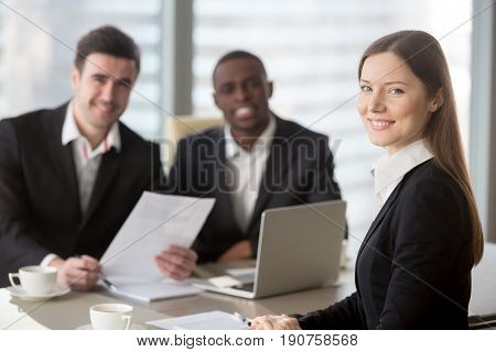 Attractive young businesswoman smiling for camera sitting at desk, young executive manager holding business meeting for black and white subordinates clients at background, female team lead portrait