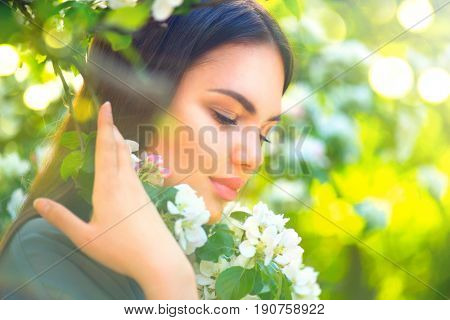 Beauty young woman enjoying nature in spring apple orchard, Happy Beautiful brunette girl in Garden with blooming apple trees. Smiling Person smelling blossom flowers outdoors
