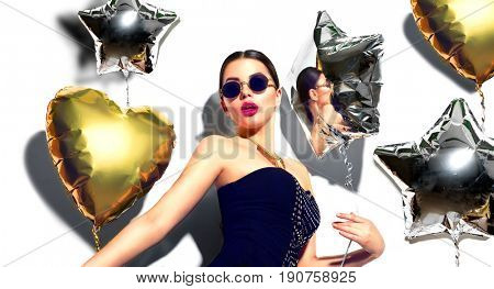 Beautiful fashion model party girl with colorful heart and star shaped balloons posing in studio in sunglasses, isolated on white background. Beauty gorgeous sexy woman celebrating. Holiday make up