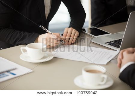 Close up of female hand holding pen, about to sign official paper, putting signature on legal document, ink deal, enter conclude contract for services, work and supplies, bilateral basic agreement