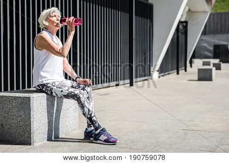 Thirsty old woman is sitting on huge granitical block near stadium building and drinking water from special bottle. Copy space in right side