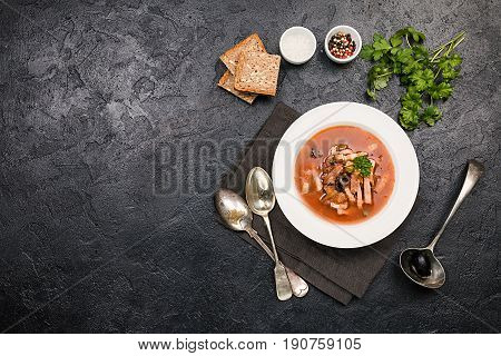 Soup with meat, olives, herbs, lemon in white bowl, black bread and spices on dark background, top view homemade food. Traditional Russian soup - solyanka