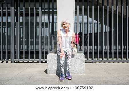 Full length portrait of pensive old lady sitting on big granitical block and holding water bottle in left hand. She is having rest after exercise near fence of stadium building