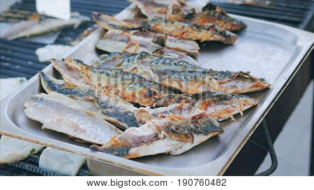 The chef toils over an open grill frying fish, rapans and squid. Cooking mackerel fillet at grill for fish durum. In-ground barbecue with fish grilling and using cooking tongs.