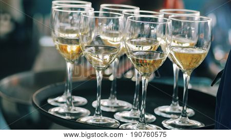 White wine glasses on a waiters tray. Waiter holds and carries out an order. Tray with glasses of alcohol drink in the restaurant.