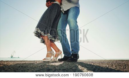 Young couple dancing latin music: Bachata, merengue, salsa. Two elegance pose on sea or ocean background. Woman in beautiful long dress.