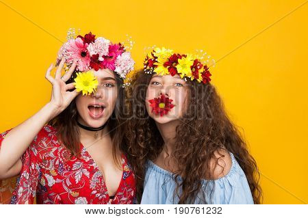 Young pretty women posing with flowers and chaplets on head.