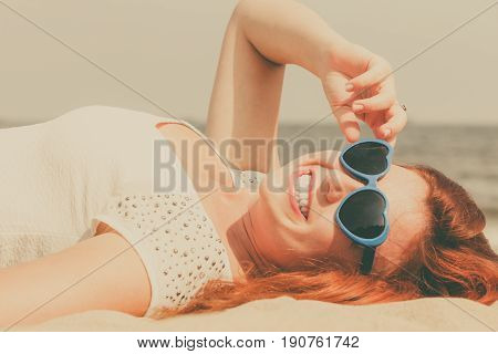 Summer relaxation and recreation concept. Happy redhead adult woman wearing sunglasses in heart shape lying on beach during summertime.