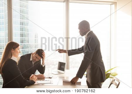 Angry bad african american boss yelling at caucasian employees, receiving reprimand with guilty and shocked expressions, showing authority, pointing at male worker made mistake, scolding for failure