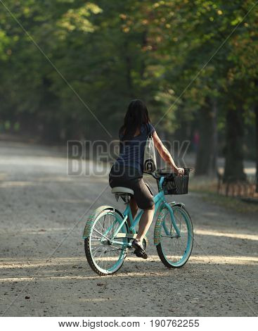 Young woman riding a bicycle in a park in the morning.