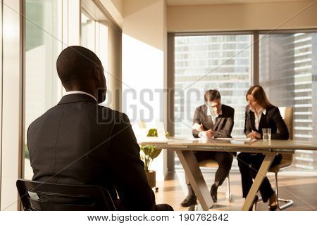 Back view at african-american applicant waiting for result after job interview while employers or hr managers consider candidature or resume, black businessman awaits for approve or reject decision