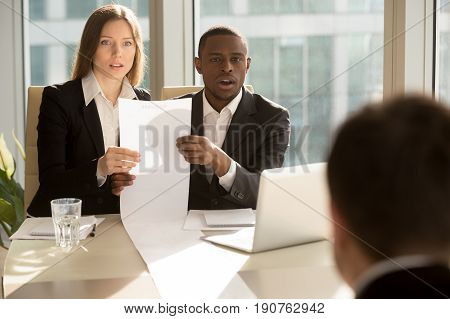 Multiracial recruiters holding long sheet of paper, looking surprisingly at candidate during job interview, prepared detailed resume with great career achievements, impressive work accomplishments