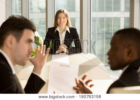 Worried nervous businesswoman waiting for result while recruiters reviewing resume, making hiring decision, unemployed young female applicant hoping to impress employer and get a job, fit a position