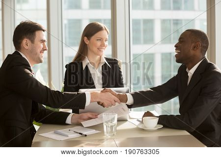 Happy smiling black and white businessmen handshaking after signing contract at multi-ethnic meeting with businesswoman, multiracial partners shaking hands, sealing closing deal with satisfied client