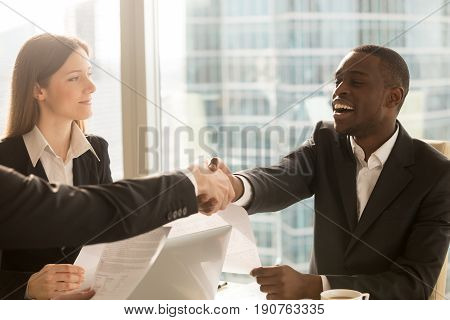 Making deal and shaking hands with smiling satisfied african-american client, multicultural partners handshaking, international businessmen signing agreement, effective negotiations under contract, HR