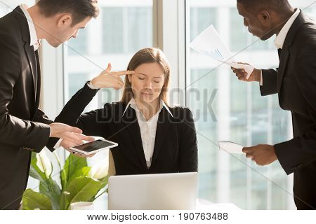 Overworked tired businesswoman puts finger gun to head, stressed with too much hard work, multitasking female boss wants to quit showing figurative gesture killing herself, exhausted of difficult job