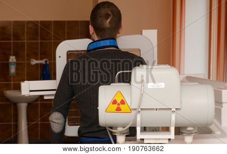 MOGILEV BELARUS - APRIL 24 2015: Young man undergoes annual mandatory fluorographic examination on digital X-ray apparatus