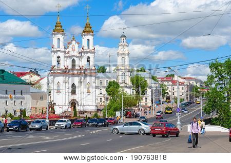 VITEBSK BELARUS - MAY 25 2017: View of Town Hall and Holy Resurrection Church Lenin Street Vitebsk Belarus. Unknown people walk down street
