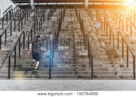 Achieving best results. Full length rear view of young man in sport clothing running up the stairs while exercising outside