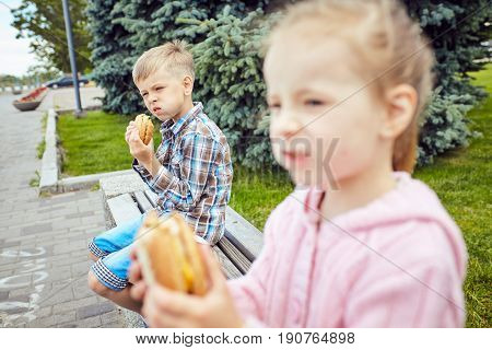 Close-up of two friends eating hamburger .