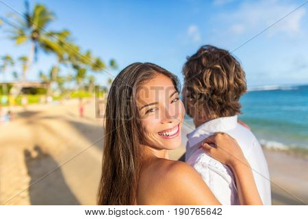 Asian beauty woman in love hugging husband on honeymoon tropical vacation portrait. Young couple lovers relaxing on beach at sunset.