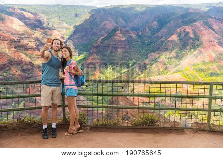 Hawaii nature hiking travel couple tourists taking selfie at Waimea Canyon lookout viewpoint. Summer vacation travelers enjoying outdoor activity in Kauai, hawaiian islands.