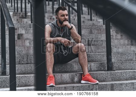 Music therapy. Handsome young man in sport clothing keeping hand on chin and looking away while sitting on the steps outside