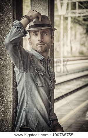 Portrait of blond haired handsome young man with fedora hat. An old train station is behind him in Italian town