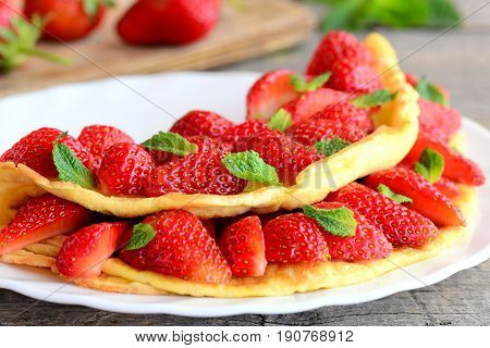 Bright stuffed omelette on a white plate. Omelette stuffed with fresh strawberries and garnished with green mint. Delicious summer recipe. Closeup