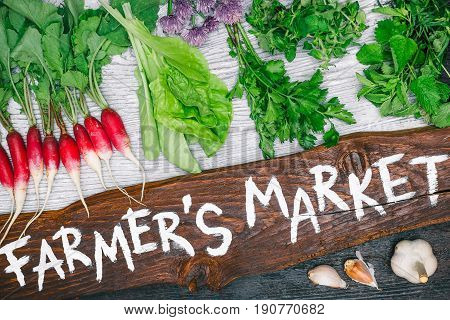 Wooden board with handwritten text 'Farmers market' and variety of fresh vegetable such as raddish, salad, cilantro, oregano and garlic on wood background. Flat lay