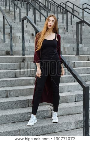 Portrait of beautiful ginger hair girl in a coat with red lips posing by the street in a city looking at camera and smiling on stairs.