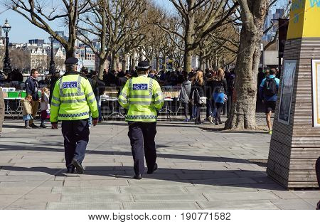 LONDON, UK - APRIL 22, 2017: London police walking on the sidewalk in the district of Westminster .