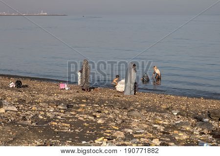 Bandar Abbas Hormozgan Province Iran - 16 april 2017: Muslim women in Islamic clothes bathe in the waters of the Persian Gulf with their children.