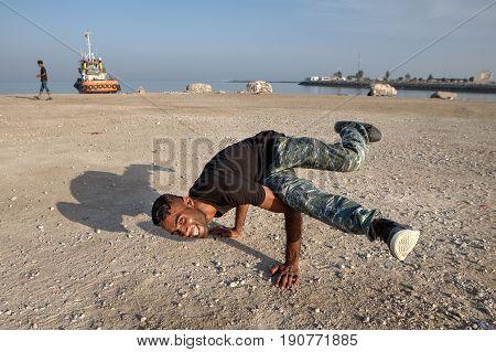 Bandar Abbas Hormozgan Province Iran - 16 april 2017: Arab youth shows the figure break dance on the beach of the Persian Gulf.