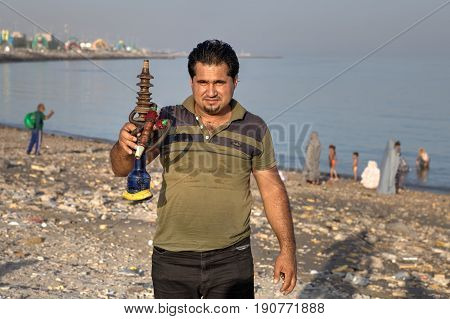 Bandar Abbas Hormozgan Province Iran - 16 april 2017: One unknown Iranian man shows a hookah on the beach of the Persian Gulf.