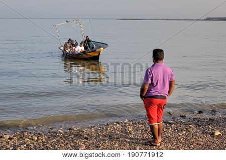 Bandar Abbas Hormozgan Province Iran - 16 april 2017: One man looks like a boat with an Iranian family aboard mooring to the shore.