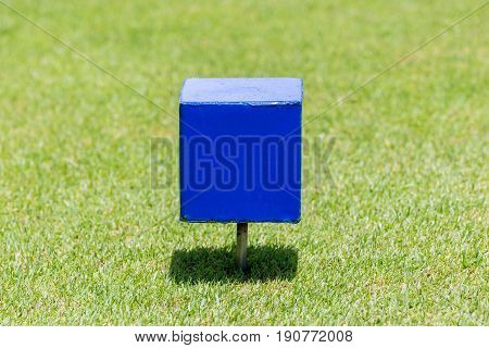 Close-up blue color wooden tee off area or tee box with blurred natural green golf course in background.